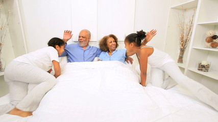 Ethnic Couple Granddaughters Relaxing Bed