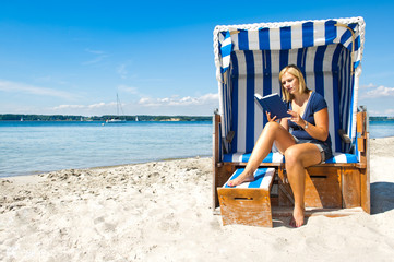 Frau beim Lesen im Strandkorb