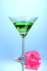 glass with cocktail and gladiolus bud