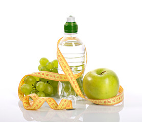 bottle with aqua, apple grapes, and measure