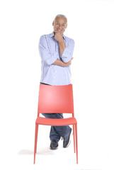 Señor de pie detrás de una silla roja.