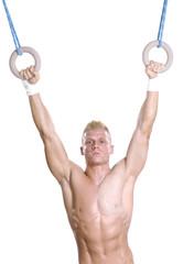 Hombre joven practicando gimnasia con anillos.