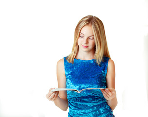 blond teenage girl reading fashion magazine