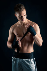 Sportsman boxer portrait against black background.