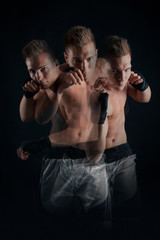 Multiple exposure boxer portrait against black background.