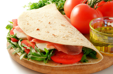 Piadina with rocket salad, raw ham, mozzarella and tomato