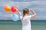 Girl at the Beach with colorful Balloons