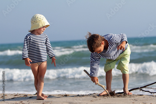 two happy children playing on beach