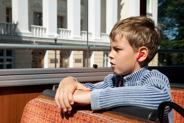 little boy riding on bus listening excursion on headphones