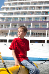 little boy sitting in front of ship in port