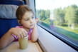 Girl sits at table near window in moving high-speed train