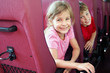 Smiling boy and girl look out from backs of seats in bus