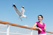 Smiling woman  feeds seagulls with bread on deck of ship.