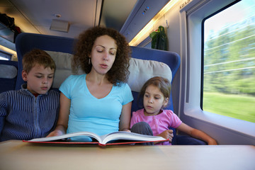 Mother reads book to her children, sitting in armchair of coach