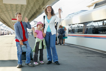 Mother with two kids and luggage stands on platform