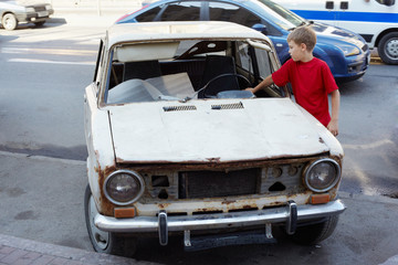 Boy in red T-shirt examines rusty with broken windshield car