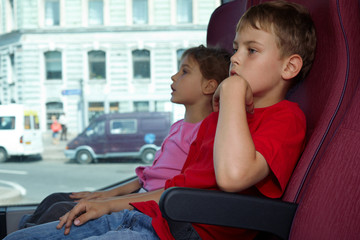Boy and girl sit in chairs in bus, side view