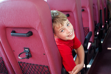 Boy, sitting in bus armchair, looks out from back of seat