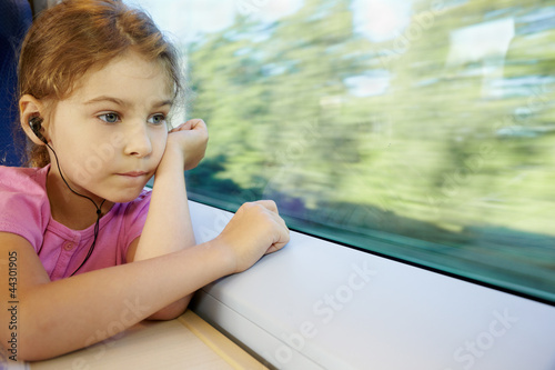 Girl listens to music, sitting by window of moving speed train