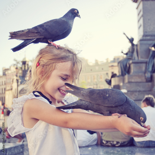 Smiling girl with pigeon on the head and the arms