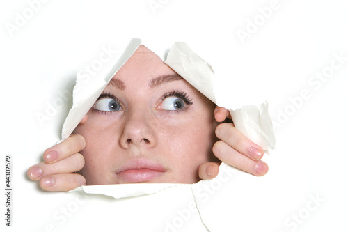 young girl looking through hole in paper