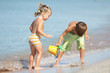 outdoor portrait of two children playing with water on sand beac