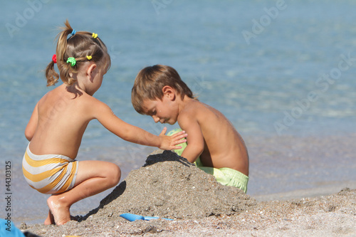 outdoor portrait of two children playing on sand beach