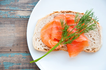 Smoked salmon on sourdough bread garnished with fresh dill.