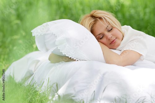 young beautiful woman sleeping on natural background