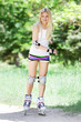 young beautiful happy woman on roller blades on natural backgrou