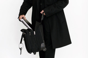 Mann packt Laptop in Tasche