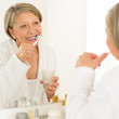 Senior woman brushing teeth bathroom mirror reflection