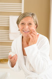 Senior woman with facial cream in bathroom