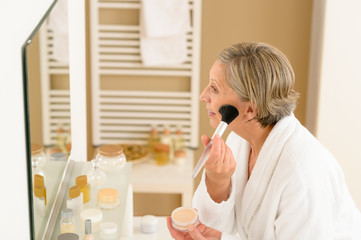 Senior woman apply make-up powder in bathroom