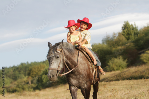 two happy children in cowboy hats riding horse on natural backgr