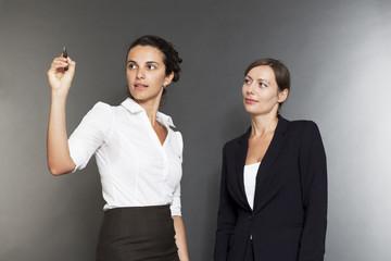 Zwei Geschäftsfrauen schreiben auf einen virtuellem Schirm