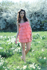 the girl with the pink dress in a meadow of flowers