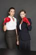 Geschäftsfrauen mit roten Boxhandschuhen