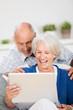lachendes älteres ehepaar schaut auf den laptop
