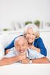 lachende senioren liegen auf dem sofa