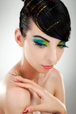 Front view of a model with multicolored make-up and nails