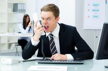 geschäftsmann schreit ungehalten ins telefon