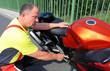 Motorradfahrer erklärt technisches Detail am Motorrad