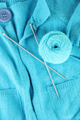 Blue sweater and a ball of wool close-up