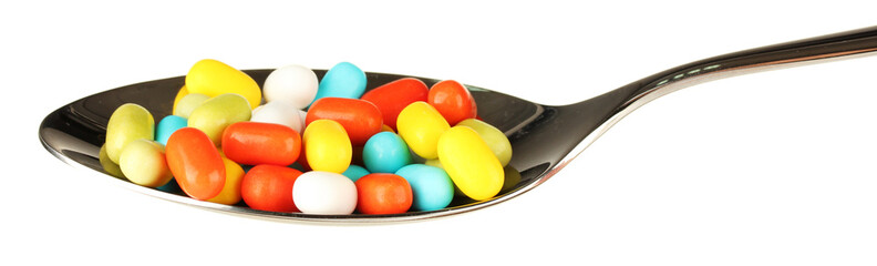 colorful pills on spoon on white background close-up