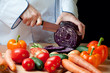 Preparing vegetables: chef cutting red cabbage-head