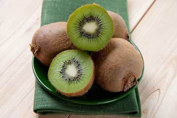 Whole and halved kiwi on a saucer, studio shot