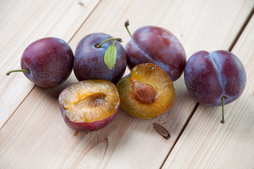 Horizontal shot of whole and halved plums on wooden boards