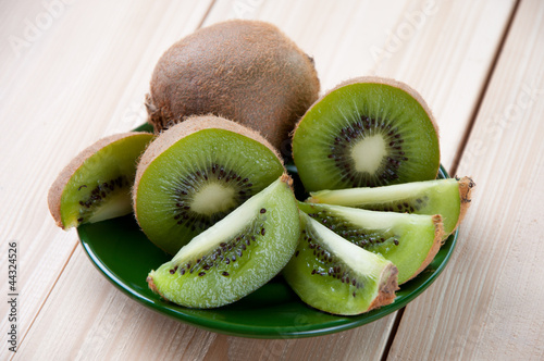 Horizontal shot of a saucer with sliced fresh kiwi