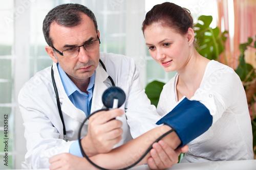 Arzt misst den Blutdruck und Puls bei Patientin